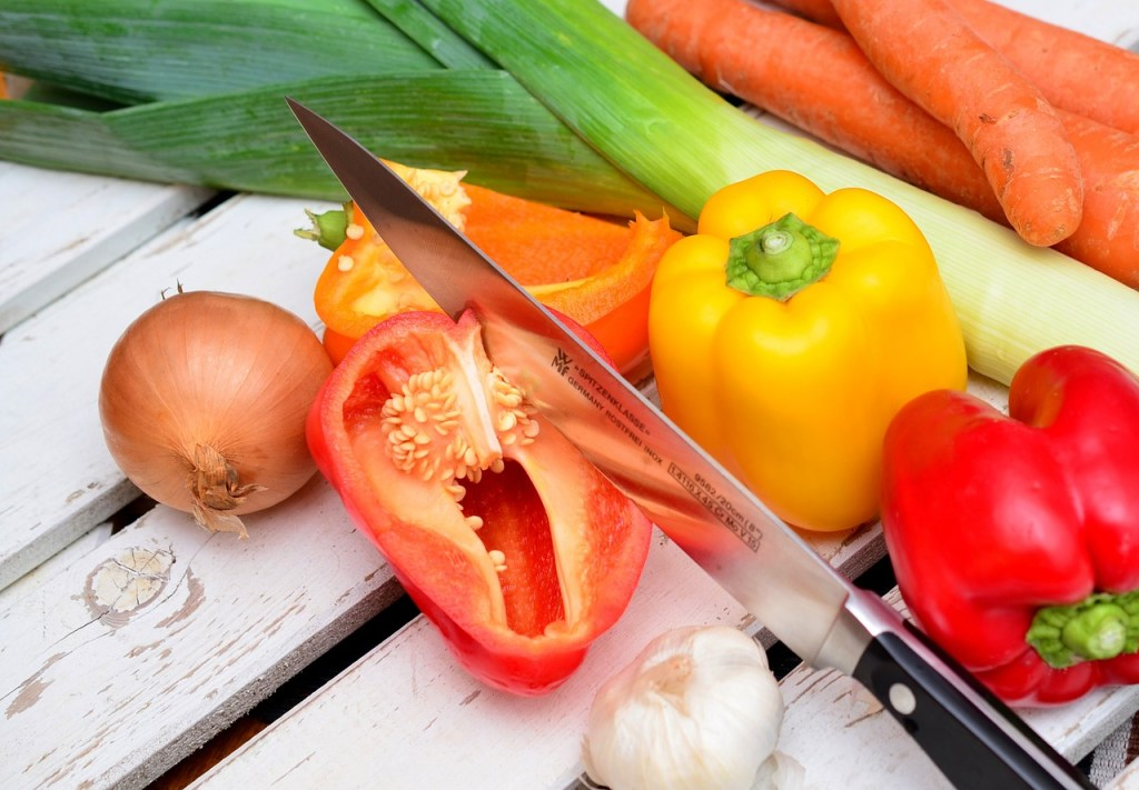 A red pepper, yellow pepper, clove of garlic, leeks, carrots, and onion lying on a white picnic table with one red pepper sliced open. The knife is lying in the middle of the vegetables.