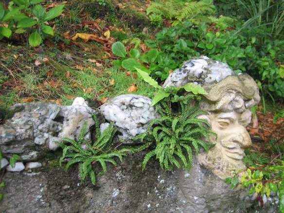 White rocks used as capping for delightful concrete wall and very weird sculpture head (Bacchus maybe)