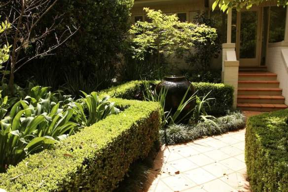 Bubbling fountain and crisp hedging make an inviting entrance