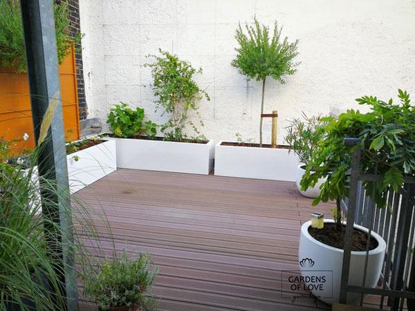 Nachher: Ein Rankgitter wurde für das immergrüne Geißblatt angebracht, sodass eine grüne Oase entstehen kann. Es ergibt sich ein spannender Kontrast zwischen Holzbelag, weißen Pflanzkästen und dem erhöten Grün. Die bestehenden Pflanzen wurden in neue Töpfe gesetzt, die mit der runden Form eine natürliche Lebendigkeit ausstrahlen und die eckige Terrasse harmonisieren.