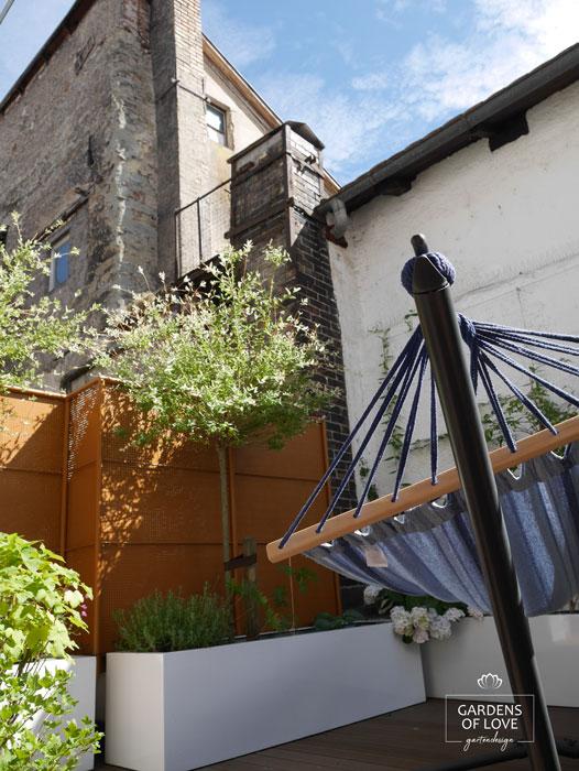 Nach 1 Jahr: auf der Hängematte können entspannte Momente im Grünen verbracht werden. Die historischen Mauern im Hinterund bilden mit der klaren Gestaltung einen spannenden Kontrast im industrial Style.