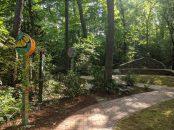 Morning sunlight illuminates the artwork,, stonework, and infinity path.