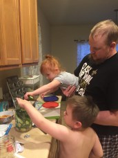 Kids helping us pack the large jar with slices and rounds of cucumbers for pickling.