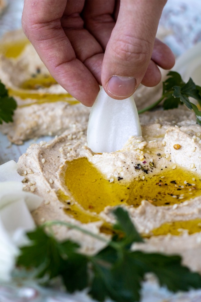 hand dipping onion wedge into hummus