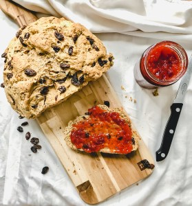 loaf of soda bread on a wooden board with one slice cut off topped with red raspberry jam