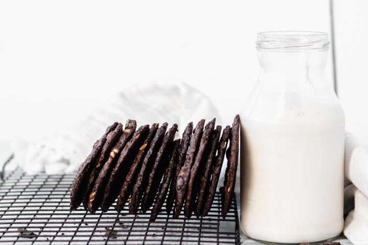 stack of tates cookies with chocolate next to a jug of milk