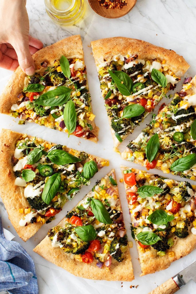 slices veggie pizza with hand reaching for one slice