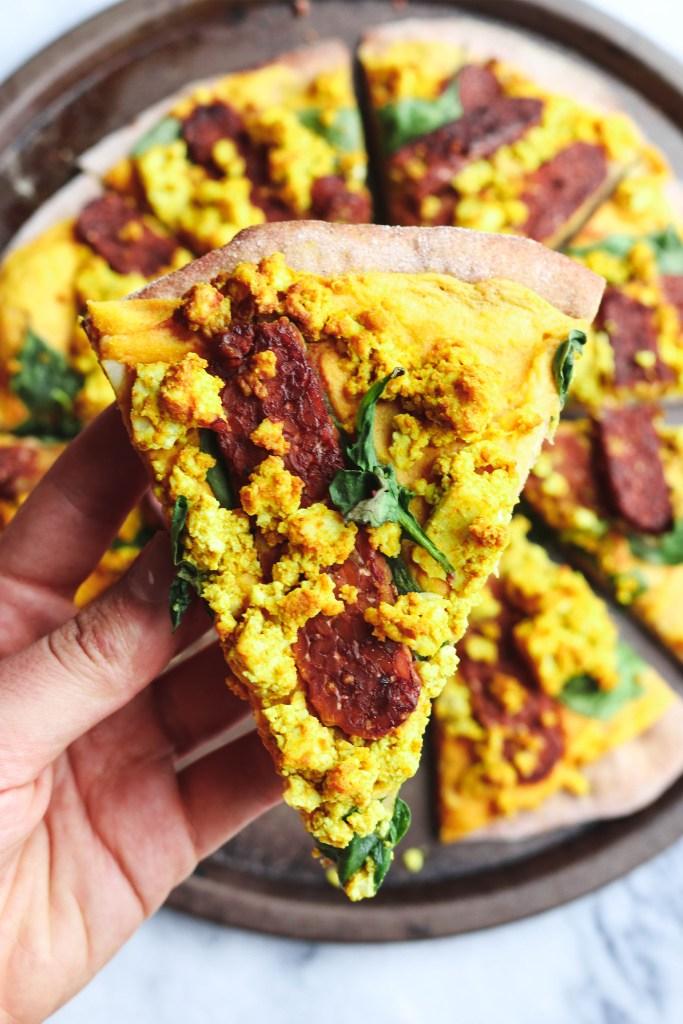 hand holding slice of cheesy vegan pizza