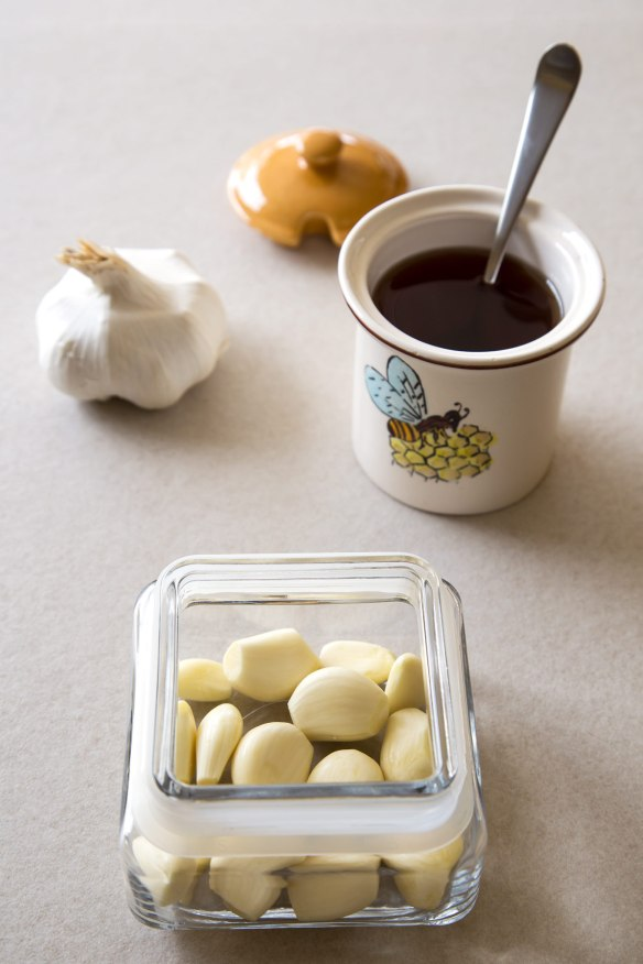 Peeled garlic cloves, jug of honey and a head of garlic on a beige counter.