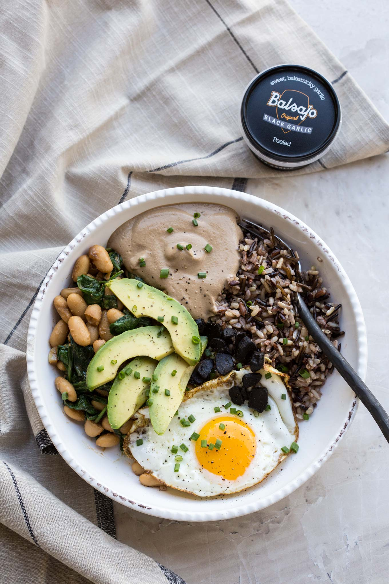 Protein Bowl with Cashew Black Garlic Sauce, Fried Egg, Beans and Avocado in a Creamy Bowl and Balsajo Black Garlic Box - birds eye view