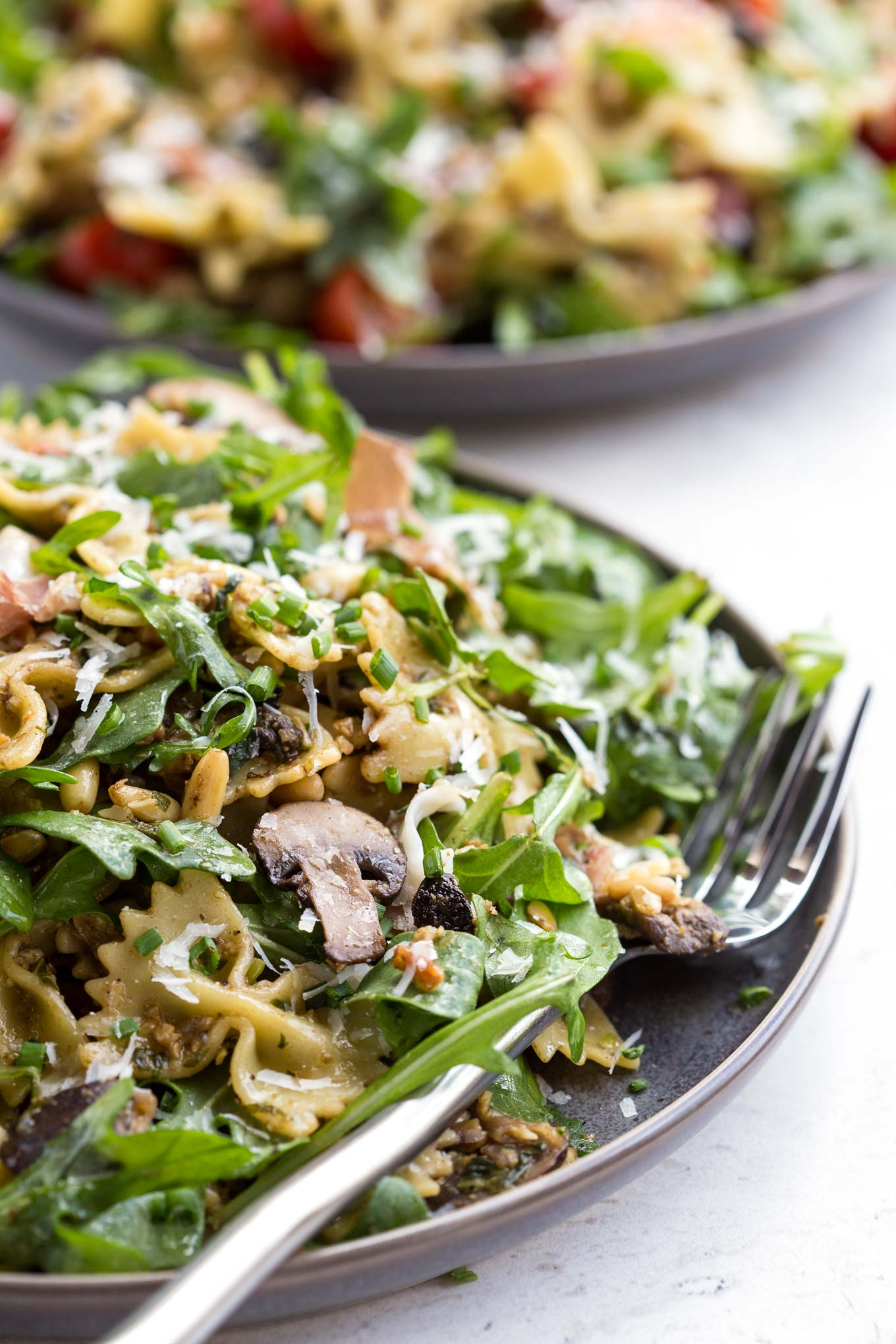 Pasta with With Homemade Black Garlic Pesto, Mushrooms, Prosciutto, Arugula and Parmesan on a Plate - 90 degree view