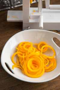 White bowl filled with raw butternut squash noodles with a spiralizer in the background
