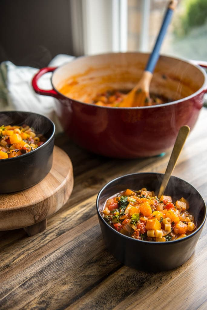 Table setting with Butternut Squash Minestrone in black bowls with a red dutch oven in background.