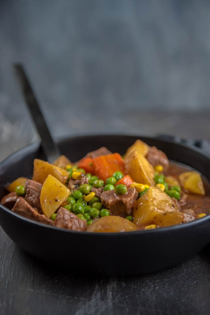 Slow Cooker Beef Stew in Black Bowl with Black Spoon