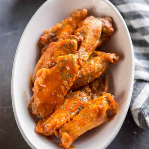 Air Fryer Chicken Wings tossed in buffalo sauce in white oval bowl