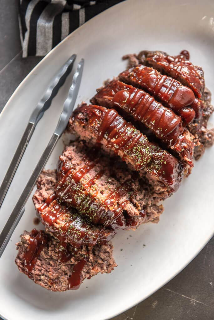 easy gluten free meatloaf sliced and topped with bbq sauce on a white platter