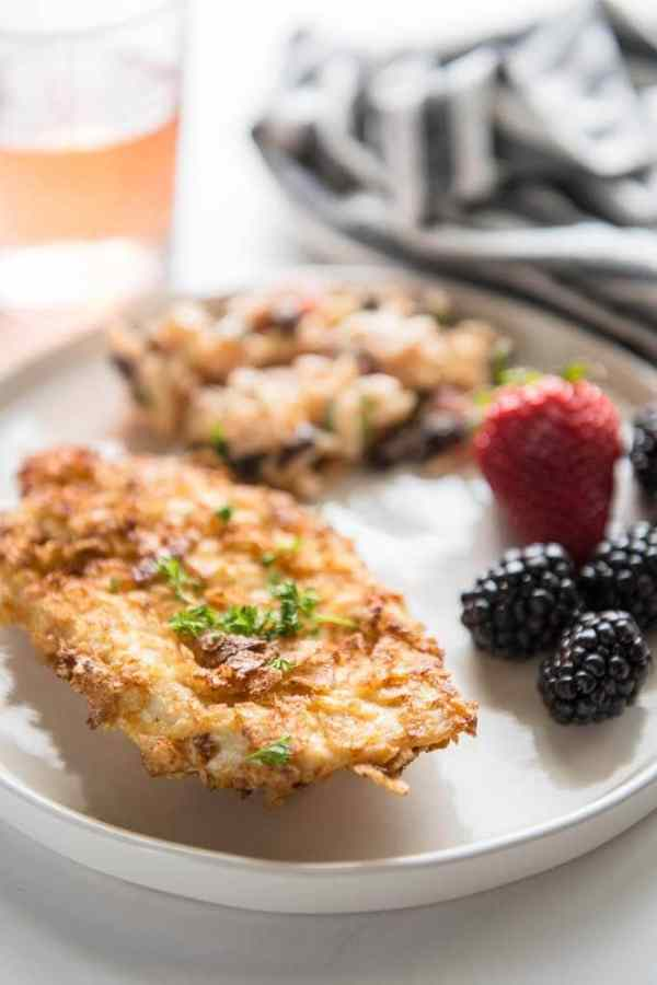 Air fryer potato chip chicken breast on white plate with pasta salad and fruit