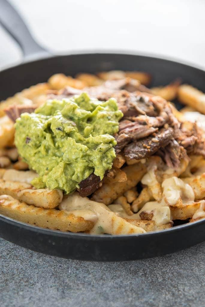 carne asada fries topped with guacamole in a cast iron skillet
