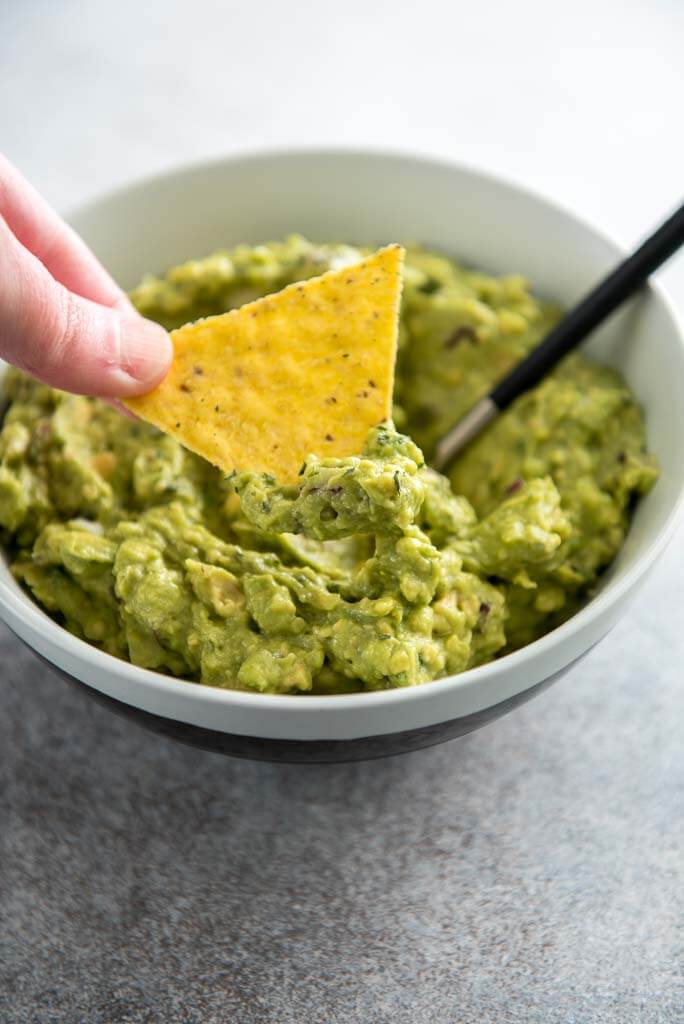 chip being dipped into guacamole in a white bowl
