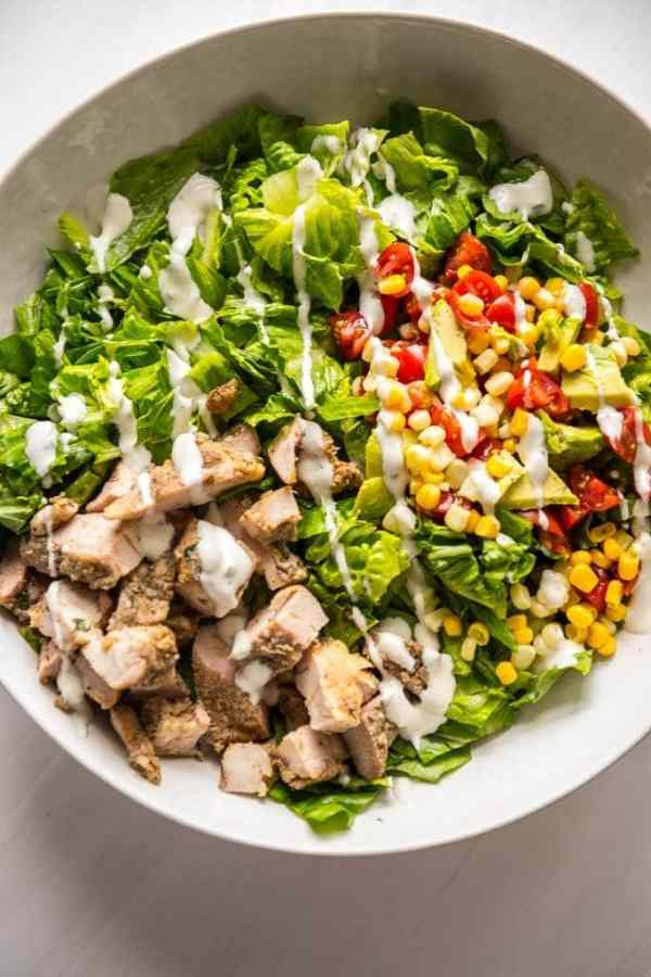 Grilled Chicken Taco Salad in white bowl with ranch dressing drizzle