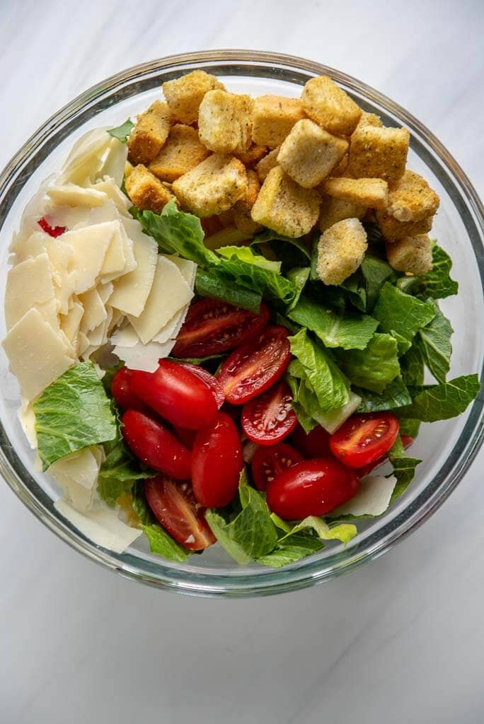 tomatoes, lettuce, croutons and cheese atop pasta in a bowl to mix for Caesar pasta salad
