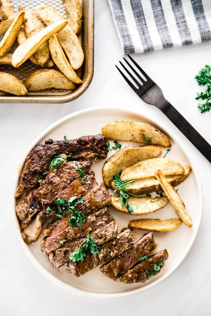 sliced skillet steak on white plate with oven fries