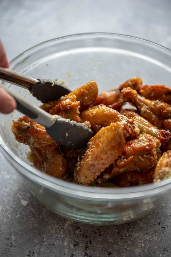 tossing chicken wings with tongs with garlic parmesan sauce
