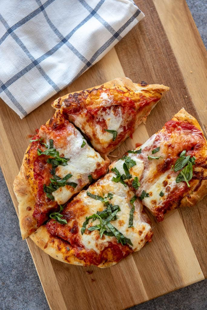 air fryer margherita pizza cut into 1/4 on wood board