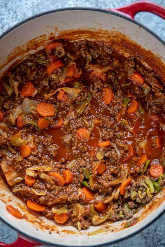 red dutch oven filled with beef and cabbage casserole