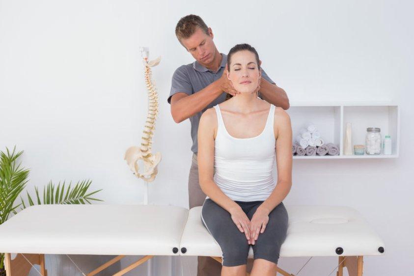 Doctor doing neck adjustment in medical office