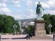 Blick vom Schloss in die Fußgängerzone von Oslo. Im Vordergrund steht eine Pferdestaue mit Reiter.