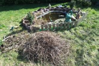 Kleiner Gartenteich mit abgeschnittenen, vertrockneten Gräsern auf einem Haufen davor.
