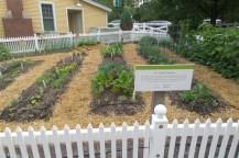 """Schild mit der Aufschrift """"The Edible Garden"""" und u. a. Mangold und Zwiebeln im Hintergrund"""