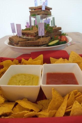 Tortilla Chips mit zwei Dips. Im Hintergrund Sandwiches auf einer Etagere.