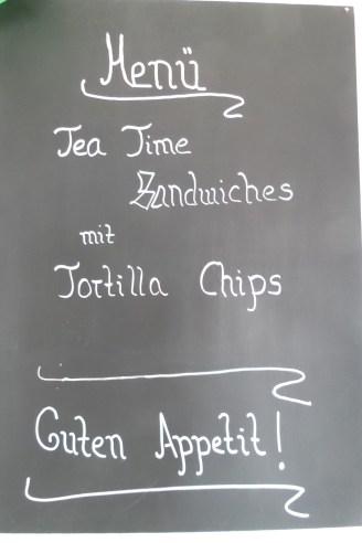 Tafel mit der Aufschrift: Menü - Tea Time Sandwiches mit Tortilla Chips - Guten Appetit!