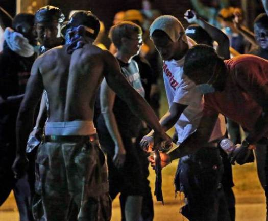 Young protestors lighting and preparing to launch a Molotov cocktail at Ferguson police.