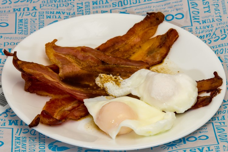 This is a photograph of Saturday breakfast. Worcestershire flavoured poached eggs with crispy bacon.