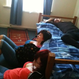 A still from Moving In. Three Students lay in a bedroom in a drunken state.