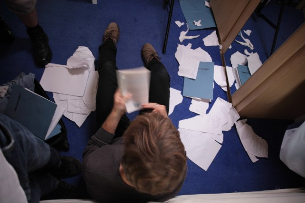 A guy surrounded by paper