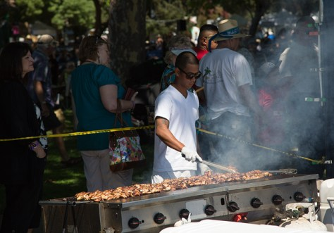 Guy barbecuing a lot of chicken at a music festival