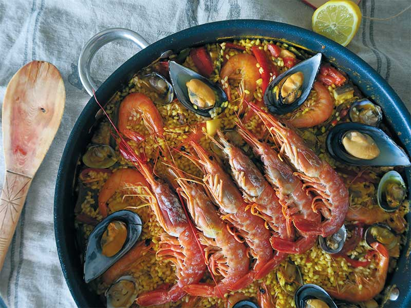 Paella de verdura y langostinos con gambones y almejas