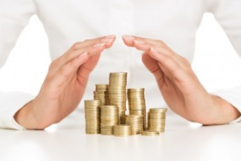 Savings protection, close up of female hands covering stack of g