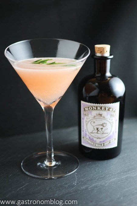 Rosemary's Blush cocktail in a martini glass with Monkey 47 gin bottle in background