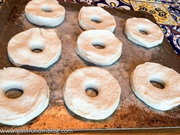 Biscuit dough cut into doughnut shape on a cookie sheet