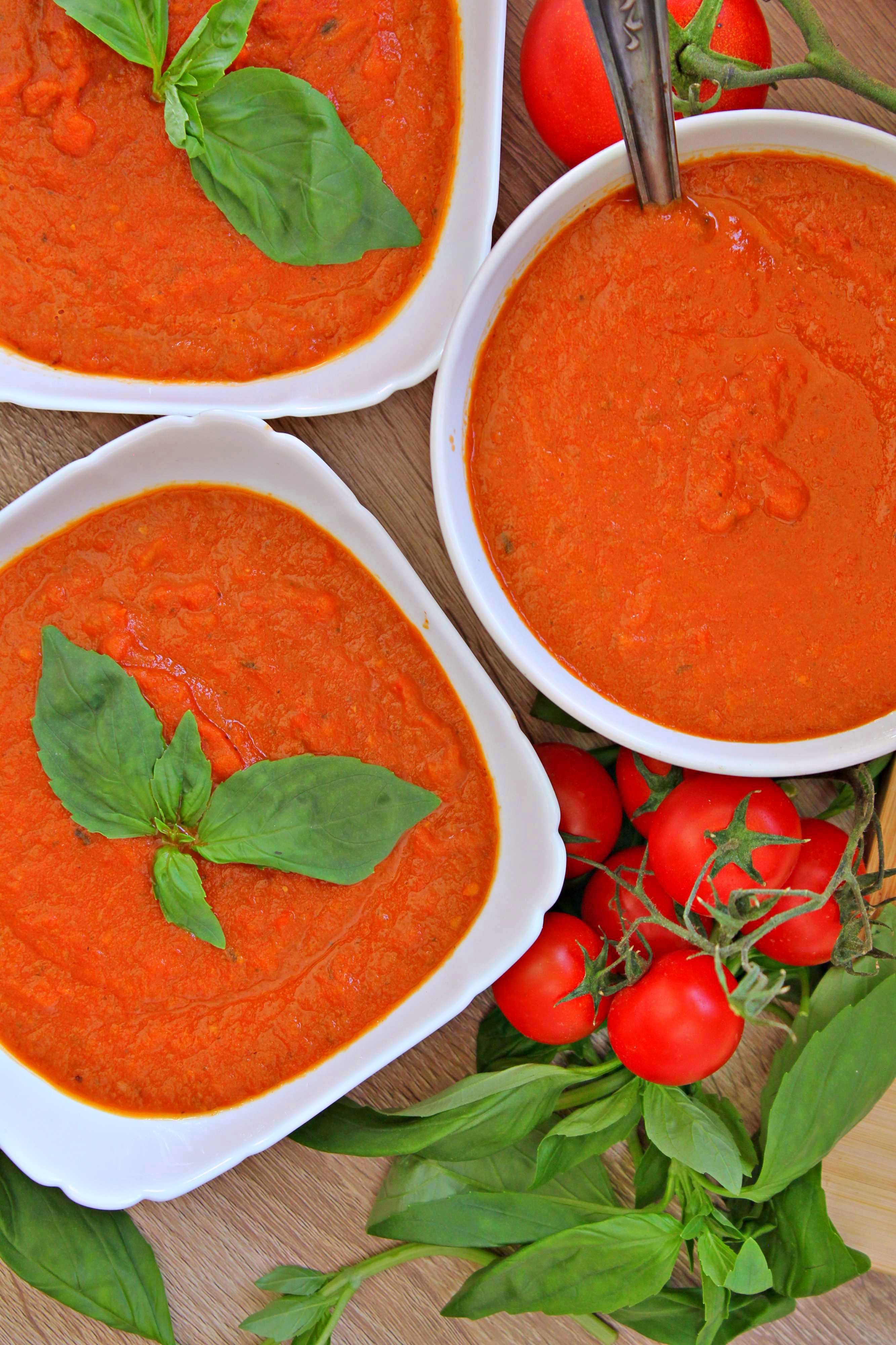 Supa de rosii coapte in 3 boluri albe, ornate cu busuioc