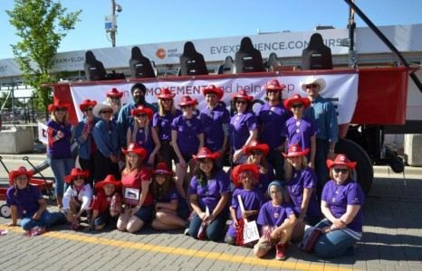 Minister Bhullar; Big Brothers Big Sisters of Calgary and Area staff, mentors and mentees; and Alberta's Promise in front of the Little Red Wagon parade float.