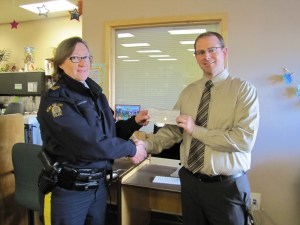 RCMP Sgt Paulina Larrey-King presenting cheque to James Holladay, Principal of Turner Valley School