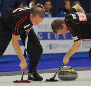 Nolan Thiessen, left, and Carter Rycroft scrub a rock during the 2011 World Financial Group Continental Cup in St. Alberta, Alta. (Photo CCA/Michael Burns)