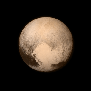 """Pluto nearly fills the frame in this image from the Long Range Reconnaissance Imager (LORRI) aboard NASA's New Horizons spacecraft, taken on July 13, 2015 when the spacecraft was 476,000 miles (768,000 kilometers) from the surface. This is the last and most detailed image sent to Earth before the spacecraft's closest approach to Pluto on July 14. The color image has been combined with lower-resolution color information from the Ralph instrument that was acquired earlier on July 13. This view is dominated by the large, bright feature informally named the """"heart,"""" which measures approximately 1,000 miles (1,600 kilometers) across. The heart borders darker equatorial terrains, and the mottled terrain to its east (right) are complex. However, even at this resolution, much of the heart's interior appears remarkably featureless—possibly a sign of ongoing geologic processes. Credits: NASA/APL/SwRI"""