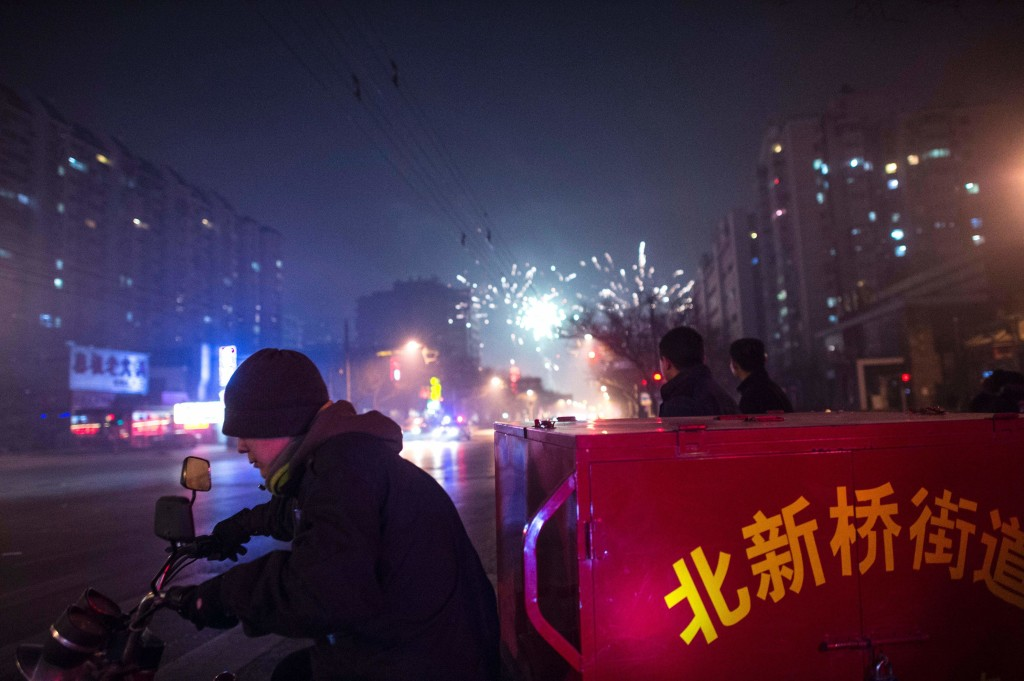 A man rides a motorcycle past people lighting fireworks on a street in Beijing on February 7, 2016, the eve of the Lunar New Year. (Getty)